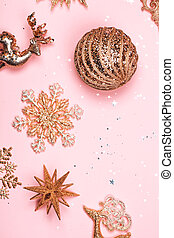 Golden beautiful sparkling christmas decorative toys on pastel pink background.