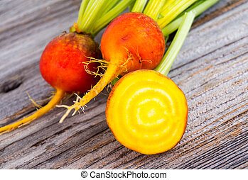 golden beets raw on rustic wood background - golden beets...