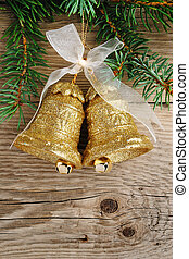 Golden bells on christmas tree on wooden background