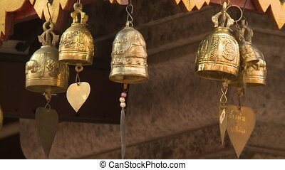 Golden bells with beads and charms - A hand held, close up...