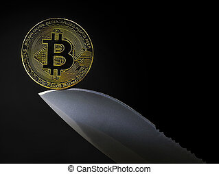 golden bitcoin coin on knife blade isolated on black background with copy space.