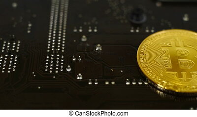Golden Bitcoin Cryptocurrency on computer motherboard. close...