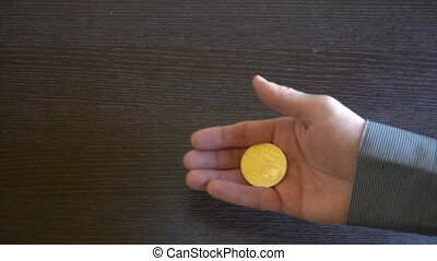 Golden Bitcoin in a man's hand. Symbol of a new virtual...