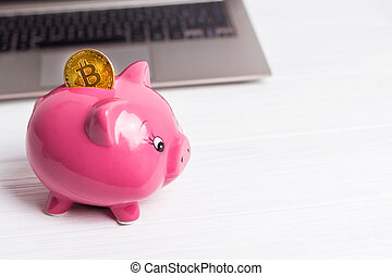 Golden bitcoin on the piggy bank money box with a computer on background. Cryptocurrency investment concept. Virtual money. Web banking, network payment