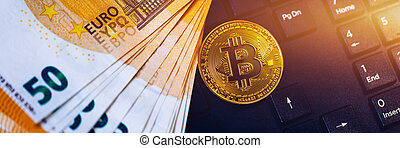 Golden bitcoin over Euro money. Bitcoin cryptocurrency. Crypto currency concept. Bitcoin with euro bills. Bitcoins stacked on euro banknotes. Computer keyboard used as background.
