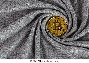 Golden bitcoin shiner on gray cotton cloth with swirl crumpling