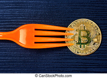 Golden bitcoin with fork on wood background