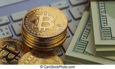 Golden bitcoins and dollar lie on the white keyboard