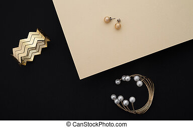 Golden bracelets with pearls and zigzag shape cuff and pair of earrings on black and beige paper background