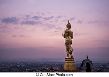 Golden buddha statue in Khao Noi temple at sunrise, Nan...