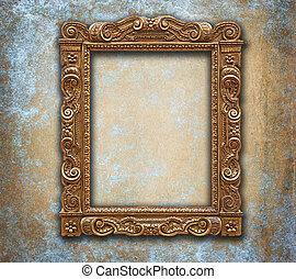 Golden carved antique frame on grunge worn wall