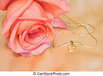 Golden chain with a heart and pink rose