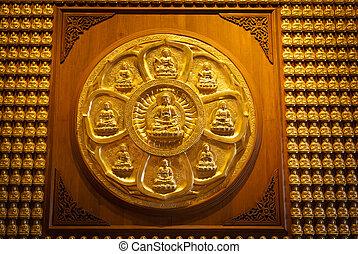 Golden chinese buddha statue on wood