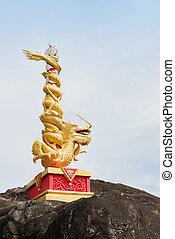Golden chinese dragon wraps around red pole