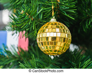 Golden Christmas ball on christmas tree with blurry France flag background, selective focus