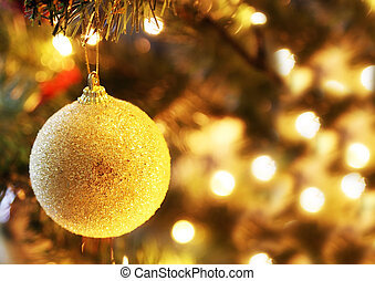 golden Christmas ball on the tree with bokeh lights background