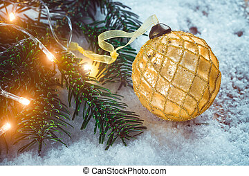 Golden Christmas ball with ribbon on snow near fir branch with bright garland. Festive background with copy space