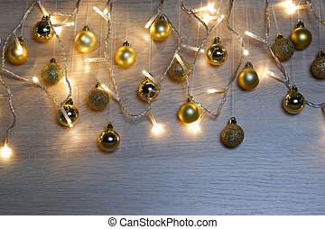Golden christmas balls hanging on threads and garland of christmas lights on light oak wood background. New year and christmas composition. Copy space