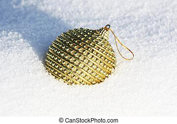 golden christmas bauble in snow