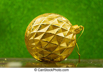 golden christmas bauble on green sparkling background