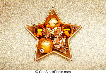 golden christmas decoration in a golden star-shaped bowl on a golden background