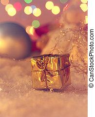 Golden Christmas gift box in snow
