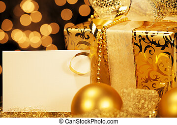 golden christmas present with christmas balls and a gift card