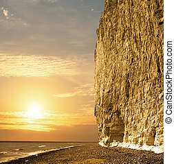 Sun setting at the coast whit large chalk cliff