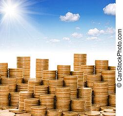 Golden coins against the blue sky