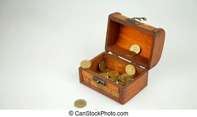 Golden coins fall from above and fill a wooden casket