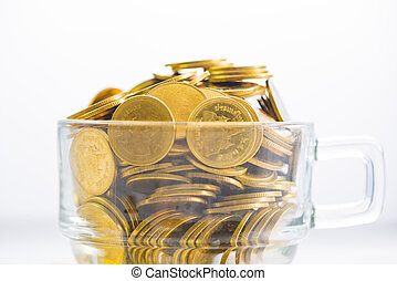 Golden coins in a glass of coffee, on the white background.