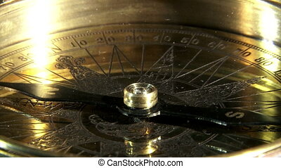 Golden compass, closeup, reflections.