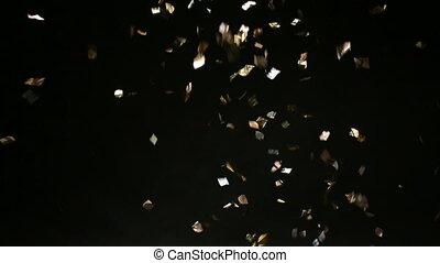 Golden confetti falling down on black background