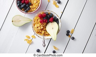 Golden cornflakes with fresh fruits of raspberries,...