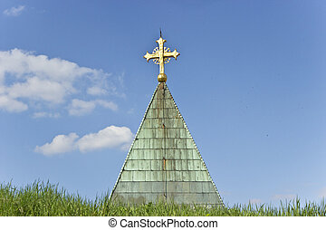 Golden cross on church over blue sky