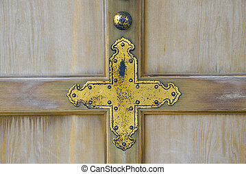 Golden cross on wooden wall
