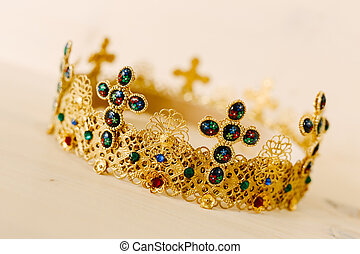 Golden crown encrusted with precious stones and crosses against a white background