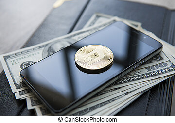 Golden Dash Cryptocurrency coin on a pile of US dollars and...