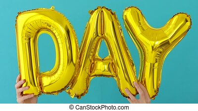 Golden DAY word made of inflatable balloons on blue...