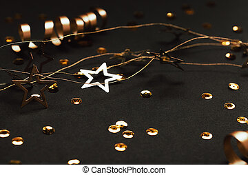 Golden decor of ribbons, confetti and star garland on black background.