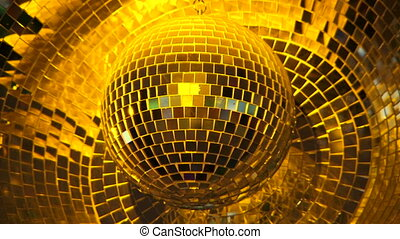 In the frame there is a big glowing disco mirror ball of golden color turning around and reflecting the rays of light during the party in nightclub.