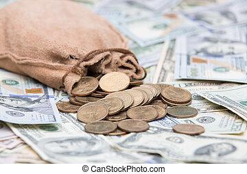 Golden dollar coins spilling from a bag