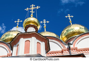 Golden domes of Russian orthodox church in Valday monastery against the dark blue sky