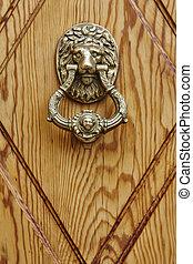Golden door knob on a wooden door. Lion head