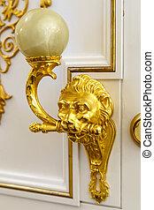 Golden door knocker in the shape of lion on a wooden door