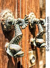 Golden door knocker with fish shape on old wooden door