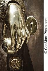 Golden doorknob on a wooden door in Spain