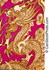 Golden dragon on the red wall of Chinese temple.