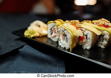 Golden dragon sushi roll with tuna, eel, cucumber, sesame ...