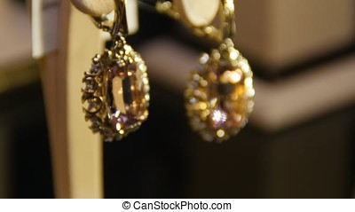 Golden earrings with gemstone. Earrings with precious stones...